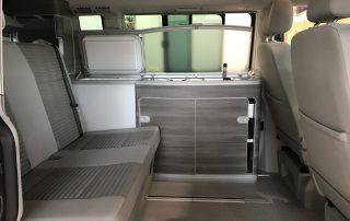 VW T6 California Innenraum mit verschiebbarer Sitzbank und Küchenzeile mit Abdeckung