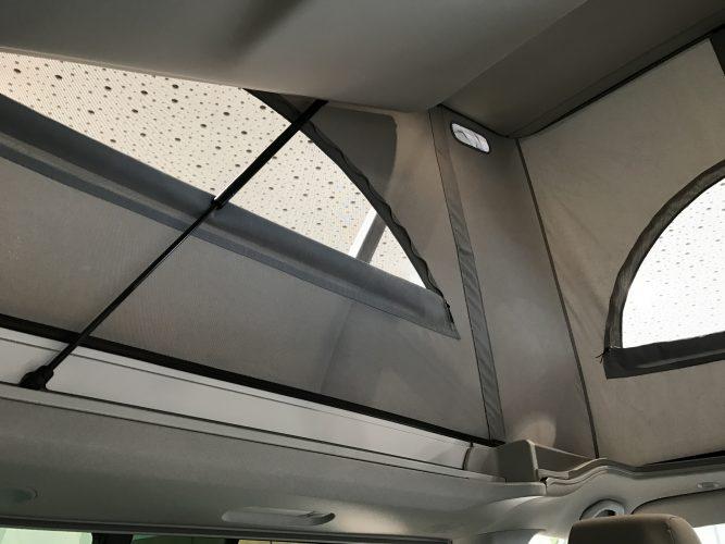 VW T6 California mit ausgeklapptem Aufstelldach mit hochgeklappter Liegefläche und Stehhöhe 1,99m im Küchenbereich