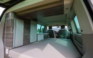 VW T6 California Ocean Innenraum mit ausgeklappter 2er Schlafbank und Komfortschlafauflage & Seitenschränken
