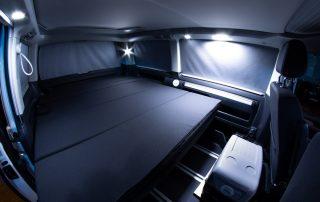 VW T6 California Beach Innenraum Bett ausgeklappt mit Innenbeleuchtung