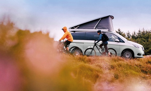 campervan and cyclists in the rain