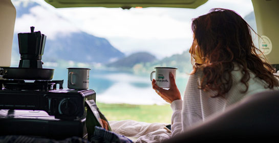 girl in a campervan with a mug